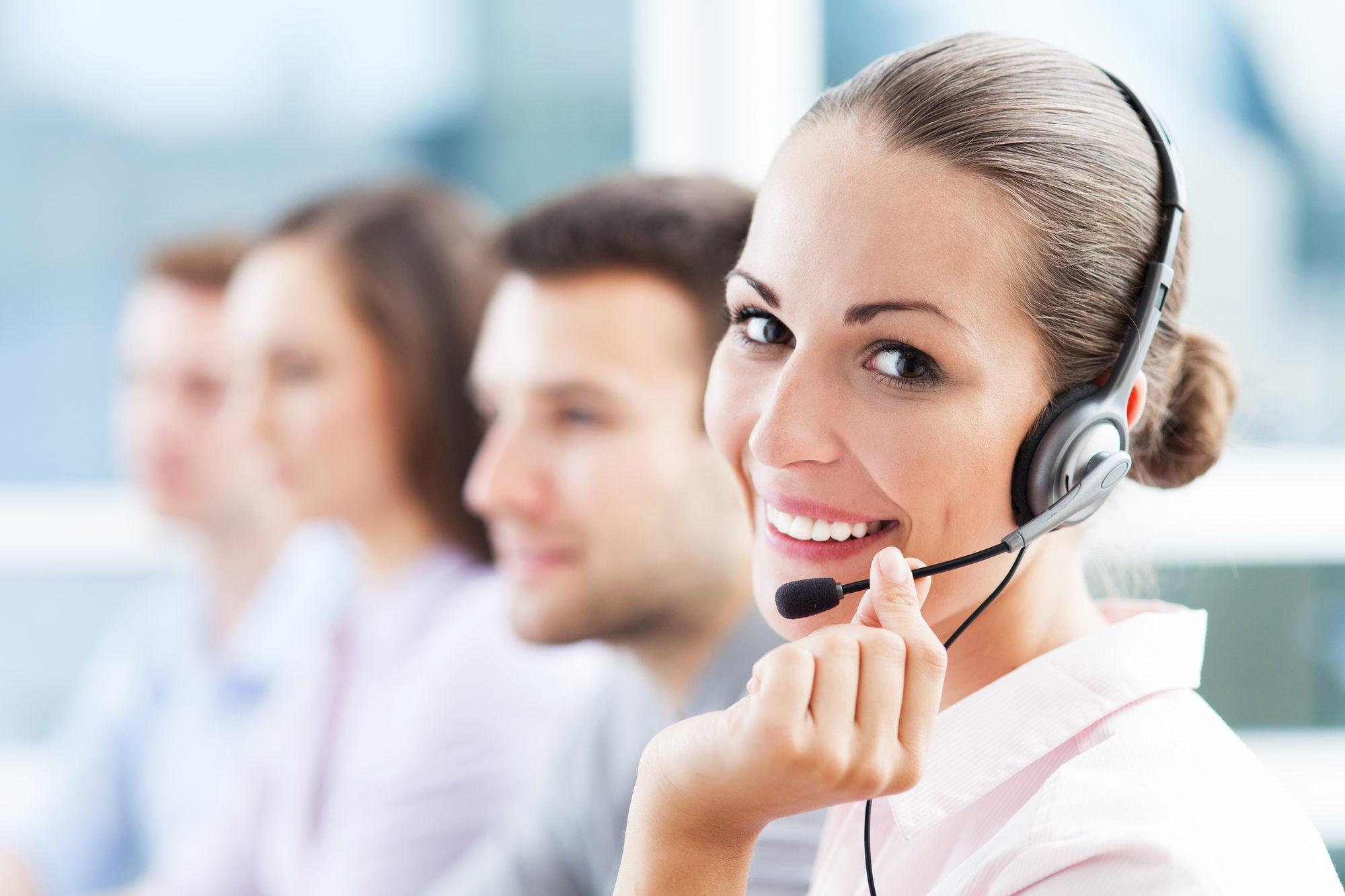 una mujer sonriente atiende al cliente por telefono